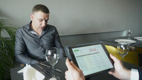 Two men in the cafe discuss the performance of the business. One looks at the tablet`s color charts and graphs. Young businessmen met in the restaurant to make stock video