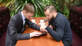 Two men at a cafe using a Tablet PC stock video footage
