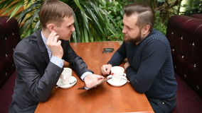 Two men at a cafe using a Tablet PC. Businessmen at lunch stock video footage