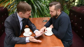 Two men at a cafe using a Tablet PC. upset. Two men at a cafe using a Tablet PC. Businessmen at lunch stock footage