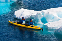 Two men in a canoe. Among icebergs in Antarctica