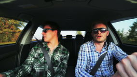 Two men in car having fun singing and dancing. In full HD stock footage