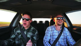 Two men in car having fun singing and dancing in a sunny day stock footage