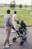 Two men carrying golf clubs in golf bags and walking at golf course. Back view of two man carrying golf clubs in golf bags and walking at golf course Stock Photo