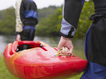 Two men carrying kayak to river Stock Photos