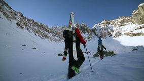 Two men carrying ski in winter mountains to the top. Close up view stock video footage