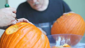 Two men carving Halloween pumpkins. Pumpkin carving by a man and his son stock video footage
