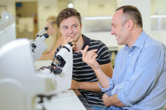 Two men chatting next to microscope Royalty Free Stock Image