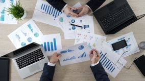 Two men checking business diagrams, discussing financial report, brainstorming. Stock photo stock photos