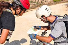 Two men are checking the map. Two cyclist men read the map on the bycicle trail Stock Photos