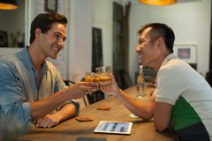 Two Men Cheers Toast Drink Ice Coffee, Asian Mix. Race Friends Guys Happy Smile Sitting at Cafe Natural Light Stock Photo