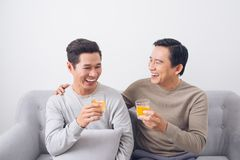 Two men clink glasses of whiskey at home, on the couch.  Stock Photography