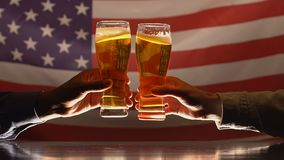 Two men clinking beer glasses against USA flag, independence day celebration