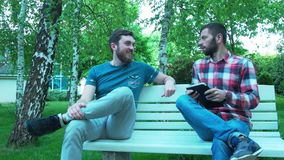 Two men communicate on a bench in the park. Meeting two friends in nature. A young man with a tablet in the air stock video