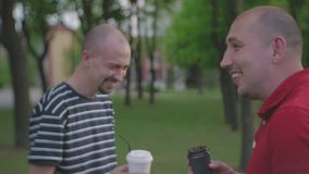Two men communicate in a city park and drink coffee from disposable plastic glasses. Two bald men communicate in a summer city park and drink coffee from stock video footage