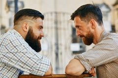 Men communicate with their views at the table. Two men communicate with their views at the table stock photos