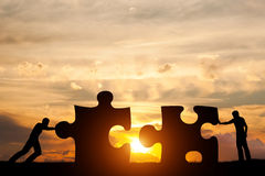 Two men connect two puzzle pieces. Concept of business solution, solving a problem. Two men connect two puzzle pieces. Sunset sky. Concept of business solution Stock Photography