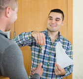 Two men with contract at apartment doorstep Stock Photography