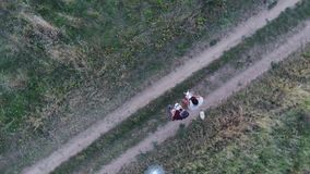 Two men controlling drones, aerial view from drone