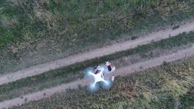 Two men controlling two drones, aerial view from drone