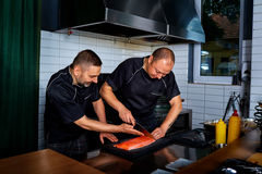 Two men cook chef cut up, cooked fish in restaurant commercial k Royalty Free Stock Image