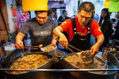 Two men cook stinky tofu at the night market of Jiufen stock photo