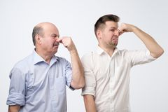 Two men cover their noses due to a bad smell. Two men father and son cover their noses due to a bad smell royalty free stock photography