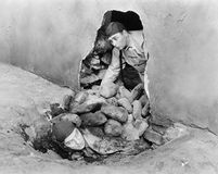Two men crawling out of a hole in a wall  (All persons depicted are not longer living and no estate exists. Supplier warranties th Stock Photography