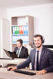 Two men from Customer service support working in the office Stock Photos