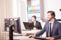 Two men from Customer service support working in the office. Two men from Customer service support working in office. Professional online and telephone assistant Stock Photo