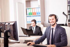 Two men from Customer service support working in the office. Two men from Customer service support working in office. Professional online and telephone assistant Stock Photography