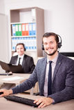 Two men from Customer service support working in the office. Two men from Customer service support working in office. Professional online and telephone assistant Royalty Free Stock Photo