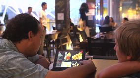 Singapore, Republic of Singapore, 25 may 2018. Two men Customers Scrolling Tablet Menu in Restaurant. 3840x2160. Two men customers scrolling tablet menu in stock video footage
