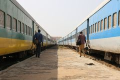 Two people at the station walking between two similar trains. Two men at dakar station walking on the platform in the same direction. the two travellers are near stock images