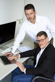 Two men at desk Stock Photo