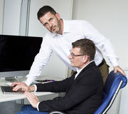 Two men at desk Royalty Free Stock Photos