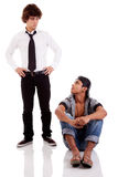 Two men of different ethnicity, one sitting lookin Royalty Free Stock Photos