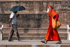 Two men from different lives. Varanasi, India - October 12, 2018: A morning scene depicting a holy Indian saint and an ordinary man passing each other royalty free stock photos