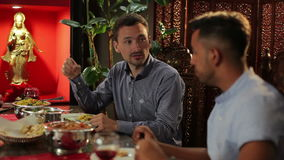 Two men dining at the restaurant. The men are sitting in the indian restaurant. The men are talking and eating indian food stock video