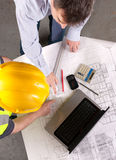 Two men discuss building plans. Elevated view of architect and builder pointing at blueprint. Focus on tabletop Royalty Free Stock Images