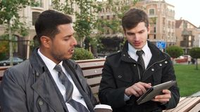 Two men discuss the information they see on the tablet. Two men are sitting on a bench in the park. One holds a tablet in his hands. He flips through the pages stock video footage