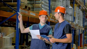 Two men discuss job matters inside a large warehouse. stock video footage