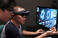 Two men discuss virtual reality with Hololens royalty free stock photo
