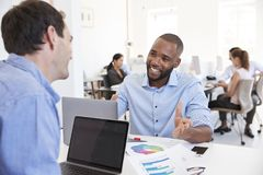 Two men discussing business in a busy office Stock Photo