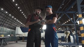 Two men discussing in aircraft hangar. Two men discussing over digital tablet in aircraft hangar stock footage