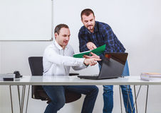 Two men discussing and pointing at computer and note book Royalty Free Stock Photo