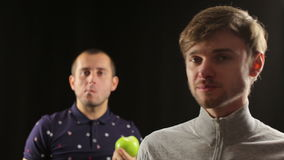 Two men do a high-five and eat apples - healthy food lifestyle portrait. Two young healthy friends do a high-five and eat apples stock video footage
