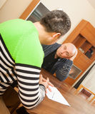 Two men with documents. Two adult men discussing something at table royalty free stock image