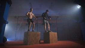 Two men doing a box jump at the gym. Crossfit training together. Synchronized box jumping stock video footage