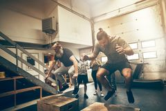 Two men doing box jumps during a workout session. Two fit men box jumping during a gym workout session with friends watching in the background stock images